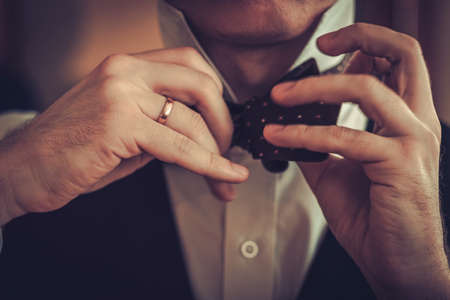 Man tying custom made bowtie