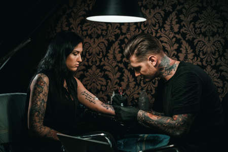 Professional tattoo artist makes a tattoo on a young girls hand Imagens