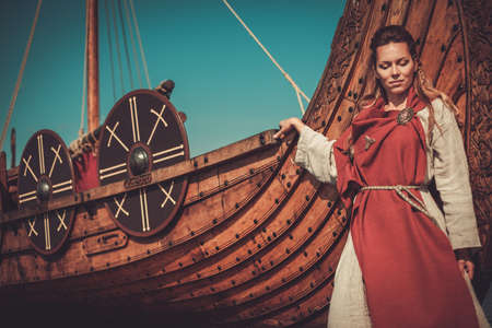 Viking woman in traditional clothes near drakkar
