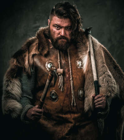 Viking with cold weapon in a traditional warrior clothes