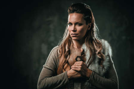 Viking woman with cold weapon in a traditional warrior clothes