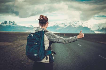 道路の上を歩いて旅行ヒッチ ハイカーの女性 写真素材