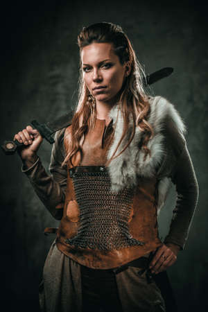 Viking woman with cold weapon in a traditional warrior clothes Zdjęcie Seryjne - 79810207