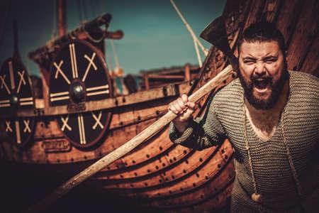 Viking with axe standing near drakkar on the seashore. Stock Photo