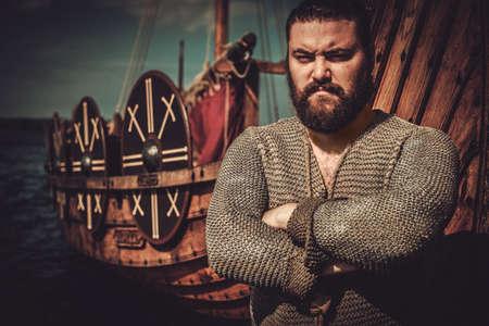 Viking with axe standing near drakkar on the seashore. Banco de Imagens