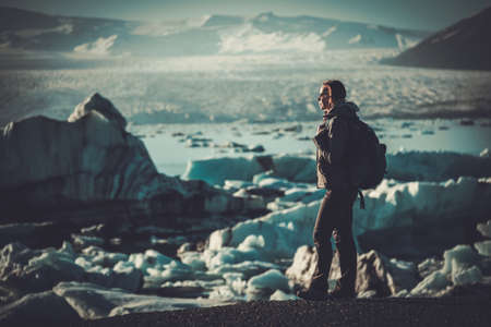 Woman explorer lookig at Jokulsarlon lagoon, Iceland. 版權商用圖片
