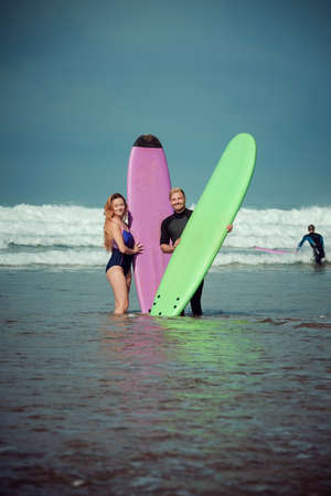 Surfer couple on the beach with a surfing board Imagens - 81814438
