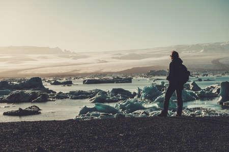 Woman explorer lookig at Jokulsarlon lagoon, Iceland. Stock Photo