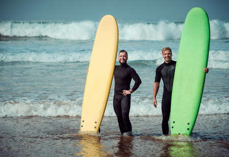 Surfer beginner and instructor on a beach with a surfboards Imagens - 81814444