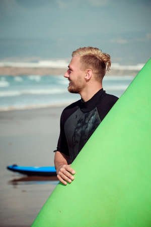 Surfer wearing wetsuit standing on the beach with a surfing board Stock Photo