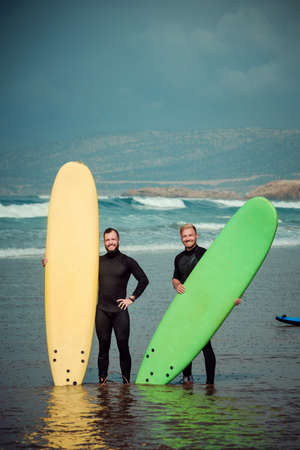 Surfer beginner and instructor on a beach with a surfing boards Imagens - 81815235