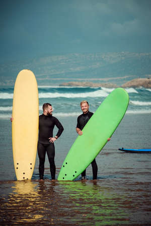 Surfer beginner and instructor on a beach with a surfing boards Imagens - 81815226