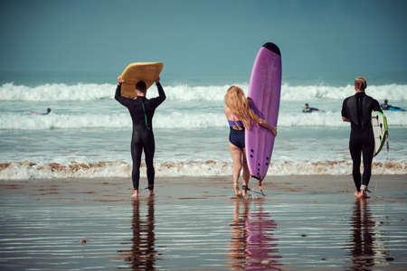 Surfer friends on a beach with a surfing boards