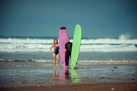 Surfer couple on the beach with a surfing board Imagens