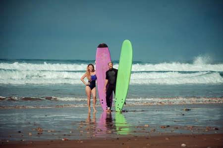 Surfer paar op het strand met een surfplank Stockfoto