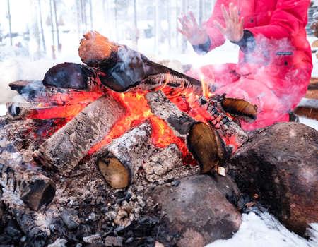 Woman near bonfire in winter landscape.