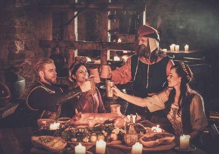 Średniowieczni ludzie jedzą i piją w starożytnej tawernie zamkowej. Zdjęcie Seryjne