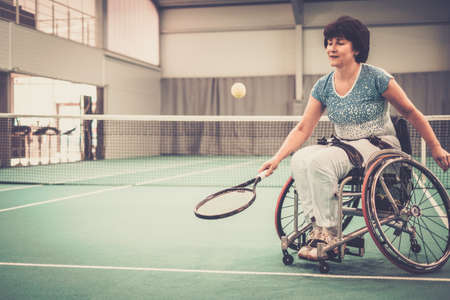 Disabled mature woman on wheelchair playing tennis on tennis court. Zdjęcie Seryjne