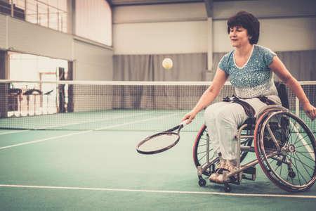 Gehandicapte volwassen vrouw op rolstoel tennissen op tennisbaan.
