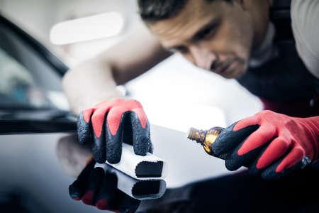 Worker on a car wash applying nano coating on a bonnet. 写真素材 - 98116383