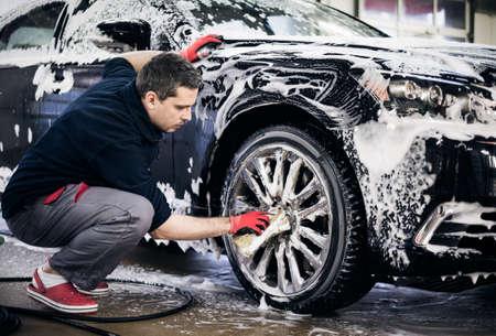 Man worker washing cars alloy wheels on a car wash. 版權商用圖片