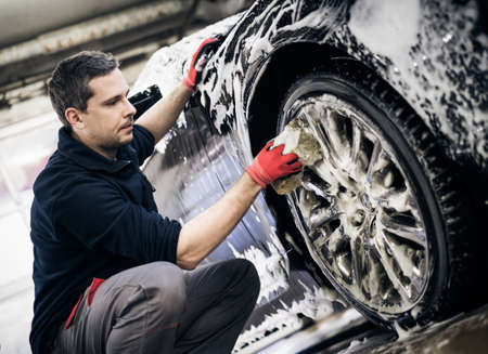 Man worker washing cars alloy wheels on a car wash. Reklamní fotografie