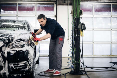 Man worker washing luxury car on a car wash.