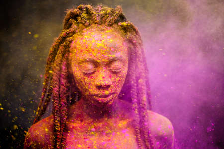 African woman with colourful powder on her face and body.