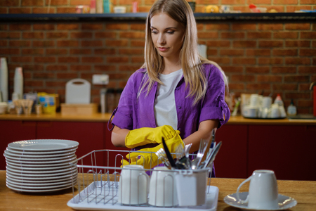 Young beautiful woman works in kitchen