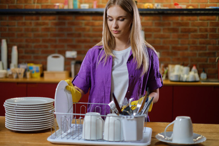 Young beautiful woman works in kitchen Stock Photo