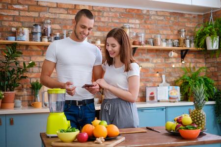Jeune couple faisant un smoothie dans la cuisine