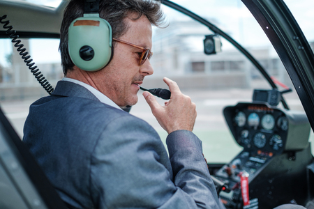 Businessman behind steering wheel of his helicopter Stock Photo