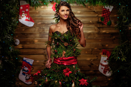 Woman in Christmas tree dress with glass of champagne and sparkler Stock Photo
