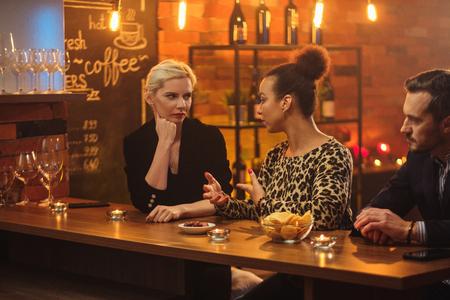 Friends having fun talk behind bar counter in a cafe