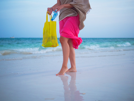 Woman collecting plastic trash on the beach