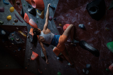 Athletic woman practising in a bouldering gym. Stock Photo