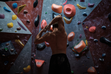 Athletic man practising in a bouldering gym.