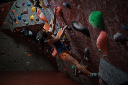 Athletic woman practicing in a bouldering gym