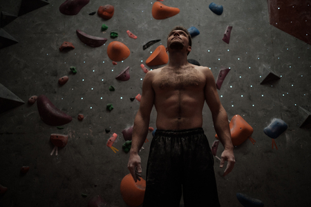 Athletic man using chalk before climbing in a bouldering gym