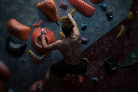 Athletic man practicing in a bouldering gym Stock Photo