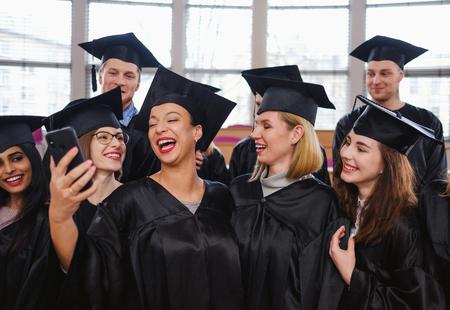 Multi ethnic group of graduated students taking selfie Stock Photo