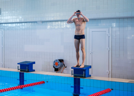 Muscular swimmer preparing to jump from starting block in a swimming pool