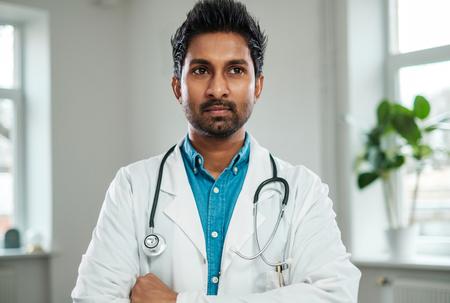 Médico indio con estetoscopio alrededor del cuello en su oficina