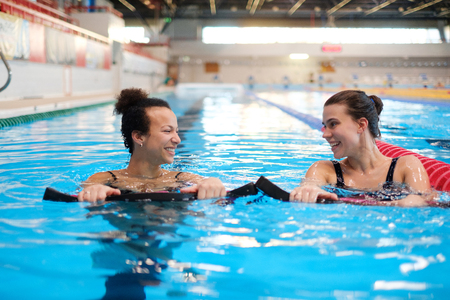 Multiracial couple attending water aerobics class in a swimming pool Stock Photo