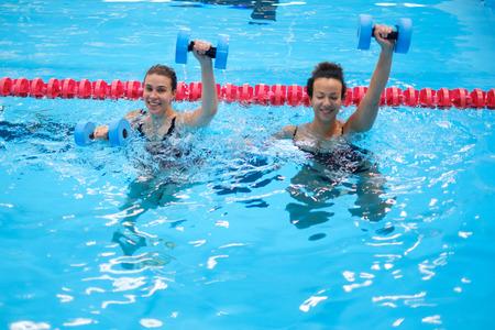Gemischtrassige Paare, die an einem Wasseraerobic-Kurs in einem Schwimmbad teilnehmen