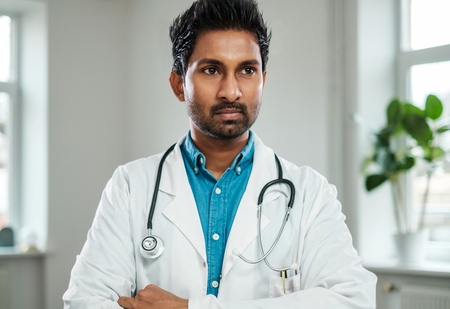 Indian doctor with stethoscope around neck in his office Stock Photo