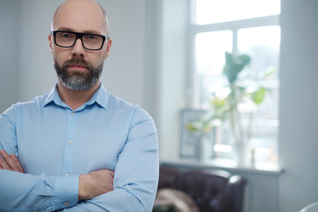 Bearded middle-aged man wearing glasses.