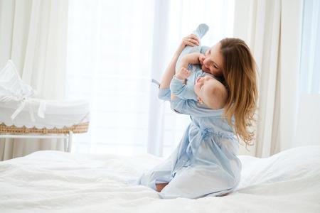 Gelukkige moeder van middelbare leeftijd met haar kind in een bed