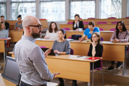 Lecturer and multinational group of students in an auditorium Фото со стока