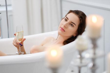 Frau liegt in einer Badewanne mit einem Glas Champagner Standard-Bild